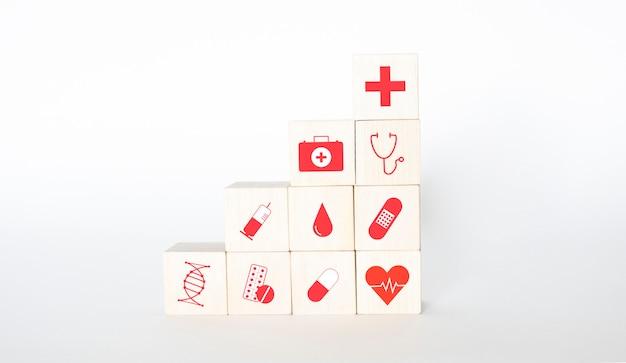 I cubi di legno sono icone di icone con miele, analisi, siringhe, compresse, pillole, cerotti e cuore. avvicinamento.