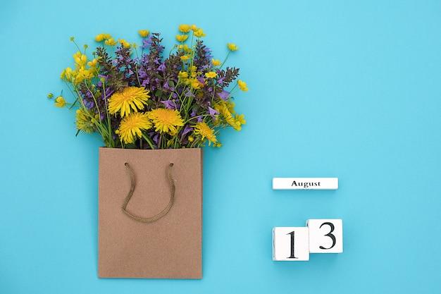 Cubi di legno calendario 13 agosto e campo fiori rustici colorati nel pacchetto del mestiere su blue.y spazio per il testo e il design