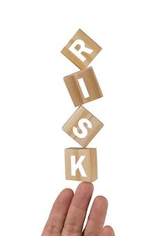 Cubi di legno contenenti lettere risk che levitano su una mano