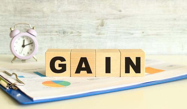I cubi di legno giacciono su una cartella con grafici finanziari su sfondo grigio. i cubi compongono la parola gain. concetto di affari.