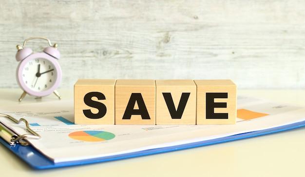 I cubi di legno giacciono su una cartella con grafici finanziari su sfondo grigio. i cubi compongono la parola save.