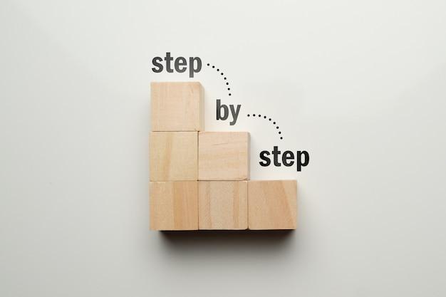 Cubi di legno a forma di scala con scala astratta passo dopo passo.