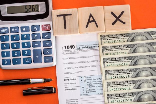 Tassa sui cubi di legno con 1040 foem, penna calcolatrice e dollaro su sfondo arancione