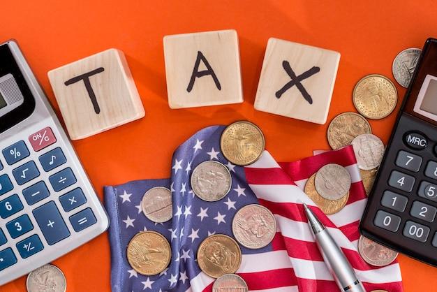 Tassa sui cubi di legno con bandiera, dollaro, moneta e calcolatrice su sfondo arancione