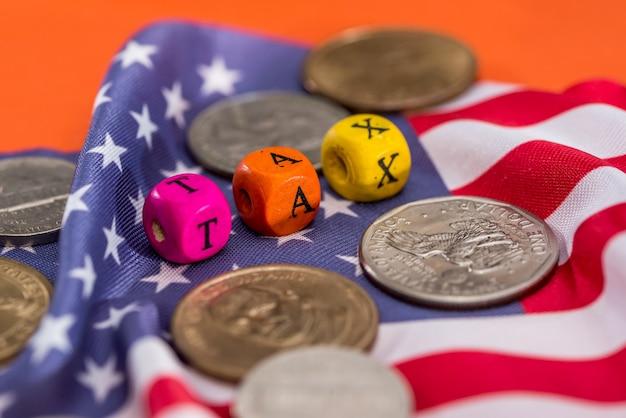 Tasse di cubi di legno con bandiera, dollaro, moneta e calcolatrice su sfondo arancione