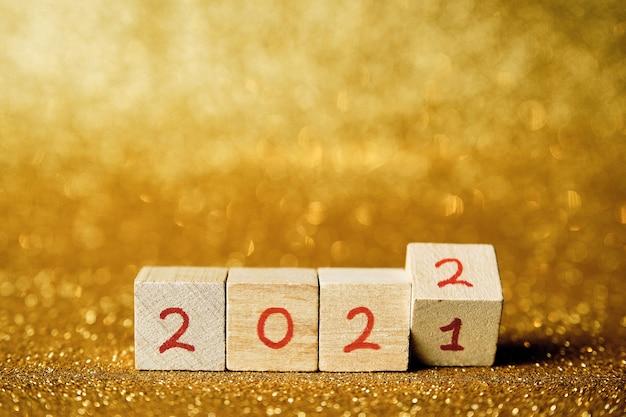 Cubi in legno con scritta 2022 in orizzontale su fondo oro lucido