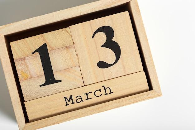 Cubi di legno con data su bianco. 13 marzo