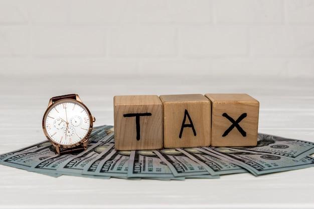 Cubi di legno con banconote in dollari e orologio da polso