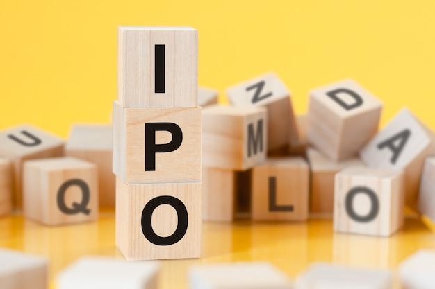 Cubi di legno con lettere ipo disposti in una piramide verticale, sfondo giallo, riflesso dalla superficie del tavolo, concetto di business. ipo - abbreviazione di offerta pubblica iniziale