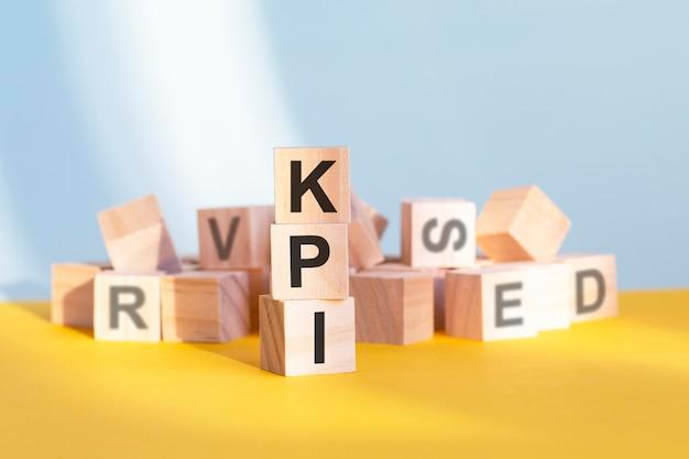 Cubi di legno con lettere kpi disposti in una piramide verticale, sfondo grigio e giallo, concetto di affari. kpi - abbreviazione di indicatori chiave di prestazione