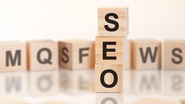 Cubi di legno con lettere seo disposti in una piramide verticale, sfondo bianco, riflesso dalla superficie del tavolo, concetto di affari. seo - abbreviazione di ottimizzazione per i motori di ricerca