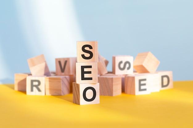 Cubi di legno con lettere seo disposti in una piramide verticale, sfondo giallo, riflesso dalla superficie del tavolo, concetto di affari. seo - abbreviazione di ottimizzazione per i motori di ricerca