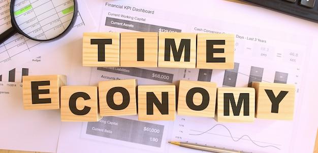 Cubi di legno con lettere sul tavolo in ufficio. testo economia del tempo. concetto finanziario.