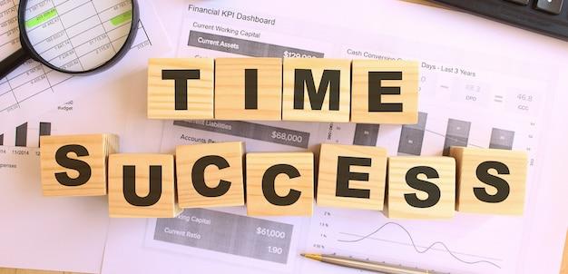 Cubi di legno con lettere sul tavolo in ufficio. testo time success. concetto finanziario.