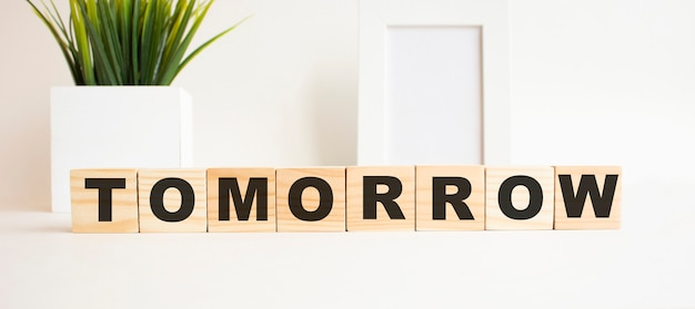 Cubi di legno con lettere su un tavolo bianco. la parola è domani. sfondo bianco con cornice per foto, pianta della casa.
