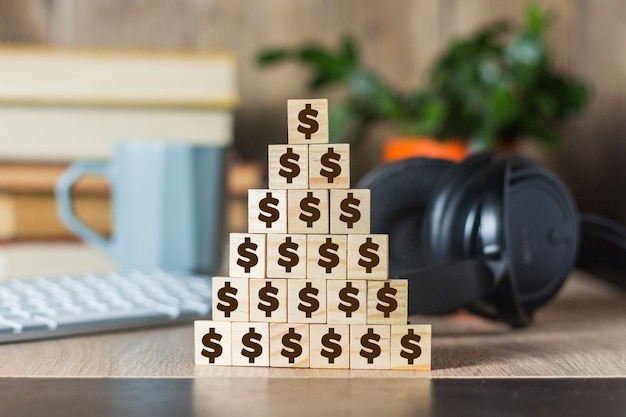 Cubi di legno con uomini allineati con una piramide e una scrivania con un computer portatile, tastiera, cuffie, tazza. concetto di corporazione, piramide finanziaria, leadership, squadra unita
