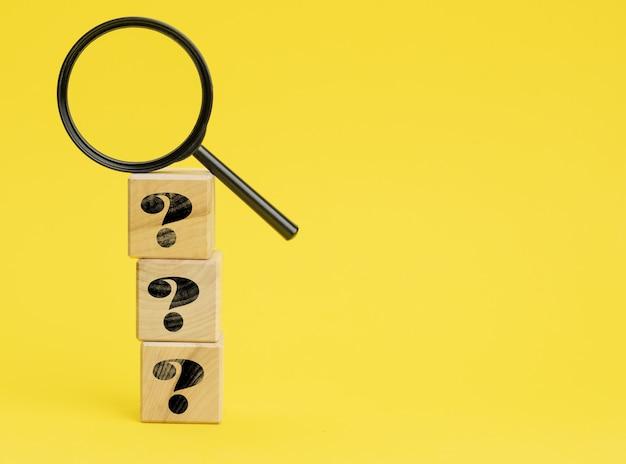 Cubi di legno con punti interrogativi e una lente d'ingrandimento su una superficie gialla