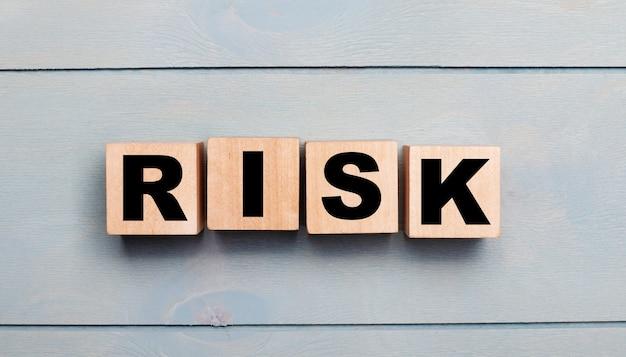 Cubi di legno con il testo rischio su una parete di legno azzurra.