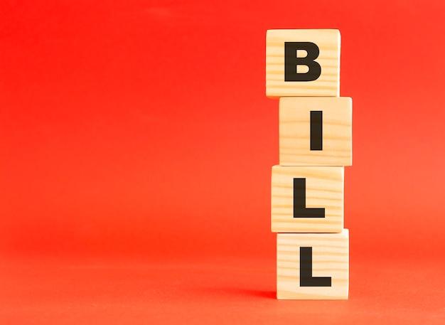 Cubi in legno con scritta bill. per il tuo design e concetto. cubi di legno su fondo rosso. spazio libero a sinistra.