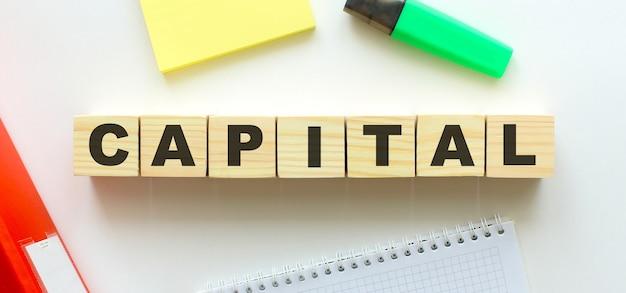 Cubi di legno con la parola capitale sulla scrivania dell'ufficio