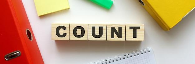 Cubi di legno con la parola count sulla scrivania dell'ufficio. cartella e altre forniture per ufficio