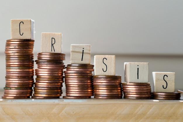 Cubi di legno con la parola crisi e mucchio di monete, scale rampicanti dei soldi, concetto di affari