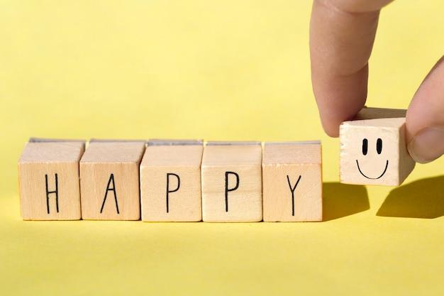 Cubi di legno con la parola felice su fondo giallo luminoso, concetto allegro