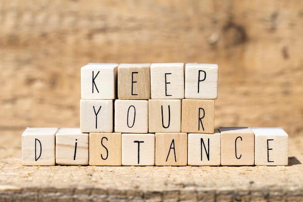 Cubi di legno con la scritta keep your distance per coronavirus e social distance. tavolo di legno