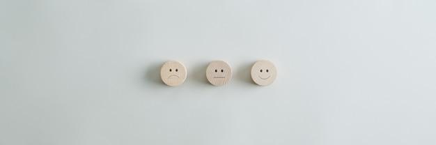 Cerchi in legno tagliati con facce che rappresentano il grado positivo, negativo e neutro disposti in fila su sfondo grigio. ampia visualizzazione dell'immagine con copia spazio.