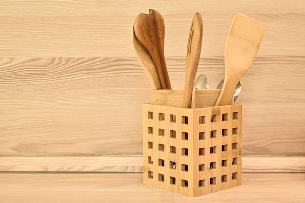 Posate di legno, spatole di bambù, cucchiai in cesto di legno sul tavolo da cucina. materiali ecologici