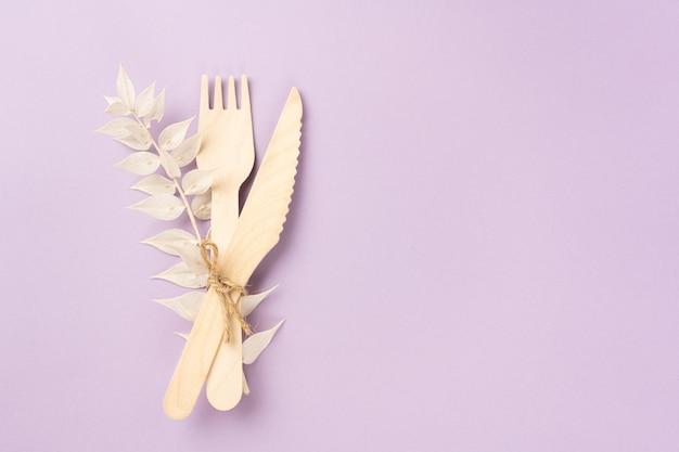 Forchetta per posate in legno e coltello da asporto con un ramo secco di un fiore su sfondo lavanda