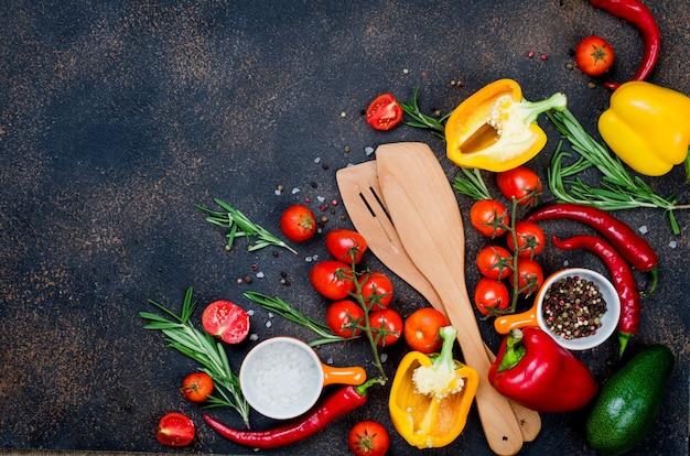 Posate in legno, verdure fresche, spezie, erbe aromatiche e ingredienti sani su sfondo scuro vista dall'alto