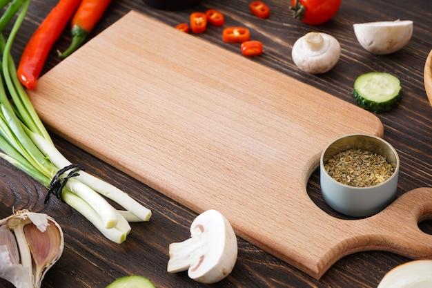 Tagliere di legno e ingredienti freschi per cucinare sul fondo della tavola in legno, primo piano