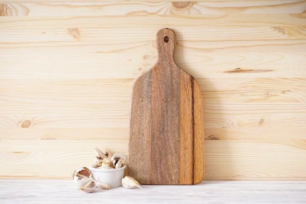 Tagliere di legno e aglio su uno sfondo di legno, posto per il testo.