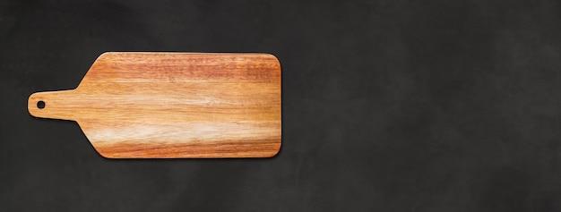 Tagliere in legno isolato su sfondo di cemento nero. banner panoramico orizzontale