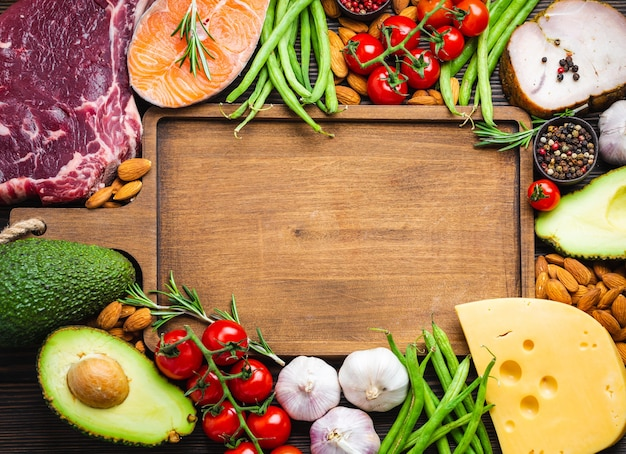 Tagliere in legno e ingredienti chetogenici a basso contenuto di carboidrati per una sana dieta dimagrante, vista dall'alto, copia spazio. alimenti cheto: carne, pesce, avocado, formaggio, verdure, noci. mangiare sano, grassi sani