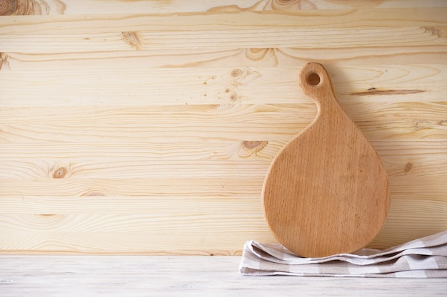 Tagliere di legno e asciugatutto su uno sfondo di legno, posto per il testo.