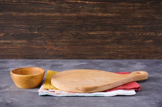 Tagliere di legno e utensili da cucina su uno sfondo di legno, posto per il testo.