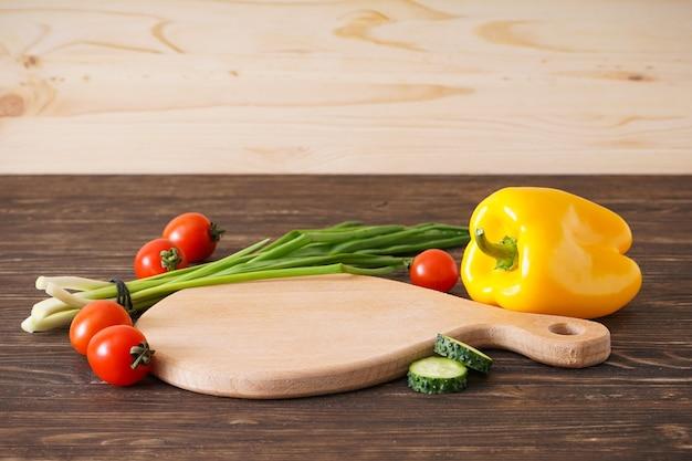 Tagliere di legno e verdure sulla tavola di legno, posto per il testo.