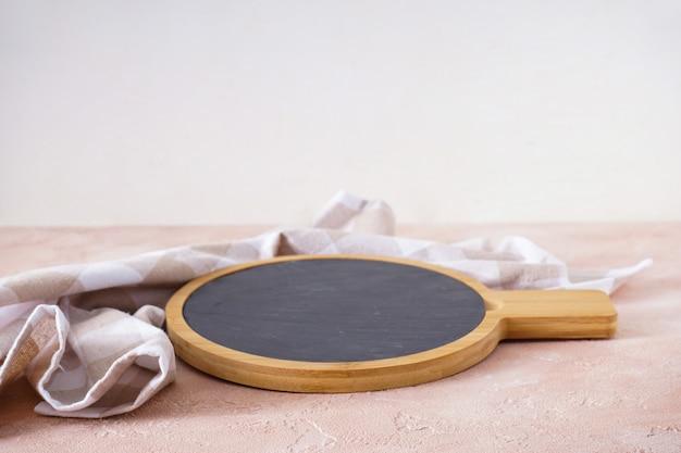 Tagliere di legno con un canovaccio su fondo beige, con spazio per il testo.