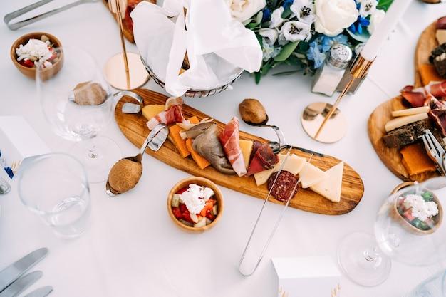 Un tagliere di legno con pezzi di prelibatezze su una tovaglia bianca al centro della festa