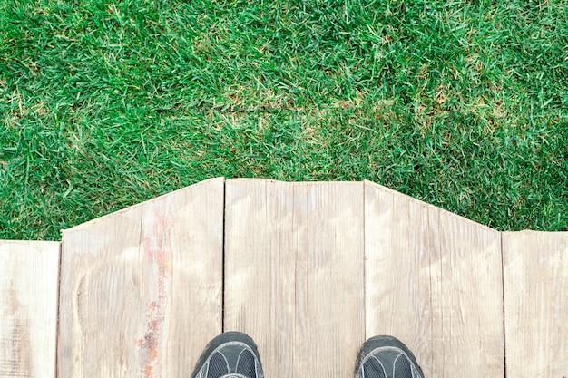 Pedana in legno con piedi ed erba verde come sfondo