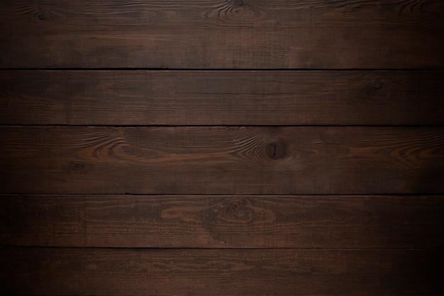 Trama di sfondo scuro in legno con vignettatura.