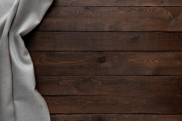 Fondo scuro in legno con tovaglia grigia.