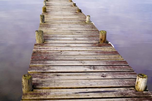 Pontone di legno del fondo del dettaglio sul lago dell'acqua con l'immagine di specchio del cielo