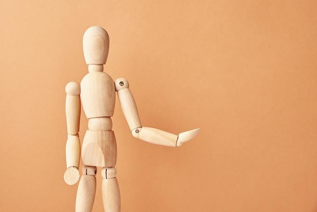 Bambola in legno su fondo beige