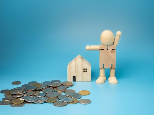 Una bambola di legno in piedi accanto a una replica di una casa in legno e un mucchio di soldi sul blu