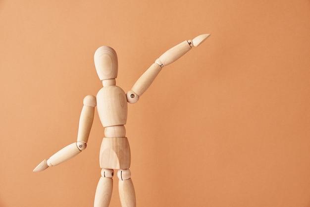 Bambola di legno con gesto su sfondo beige pastello il manichino mostra il gesto figura di umano in legno