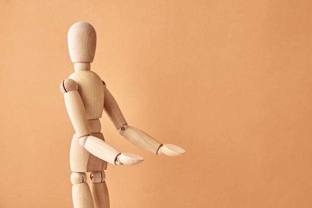 Bambola in legno con gesto su sfondo beige pastello