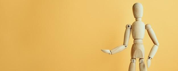 Bambola di legno con gesto su sfondo giallo manichino mostra gesto figura umana in legno